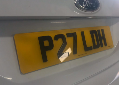 Image of a rear UK 4D number plate on a white Ford vehicle.