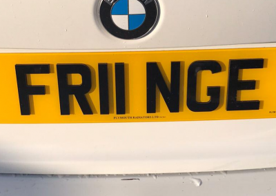 Image of a rear UK 4D number plate on a white BMW vehicle.
