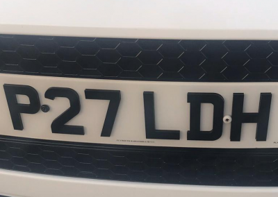 Image of a front UK 4D number plate on a white Ford vehicle.