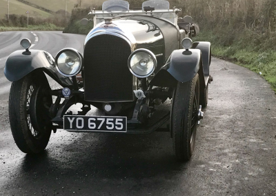 A front on image of a bottle green coloured classic Bentley motor car with a newly restored radiator, parked in a country lane.