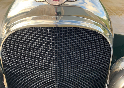 A close-up image of a bottle green coloured classic Bentley motor car with a newly restored radiator, parked in a car park.