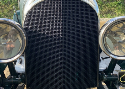 A close-up, front-on image of the newly restored radiator and headlamps of a bottle green coloured classic Bentley motor car, parked in a car park.
