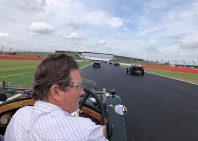 An image of a bottle green coloured classic Bentley motor car with a newly restored radiator, taking part in a classic car race.