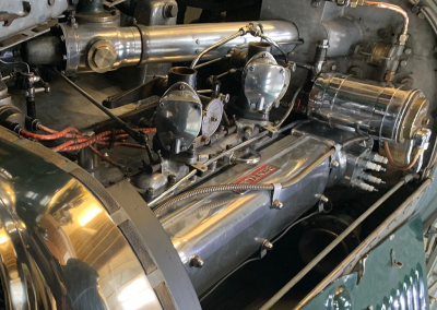 A close-up image of the radiator of a bottle green coloured classic Bentley motor car with a newly restored radiator, parked inside the Plymouth Radiators garage.