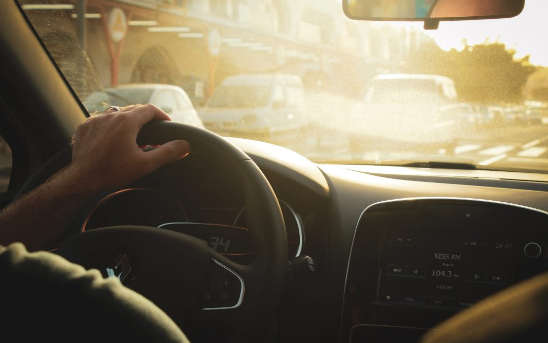 Image of a person driving a Renault car in bright sunshine.