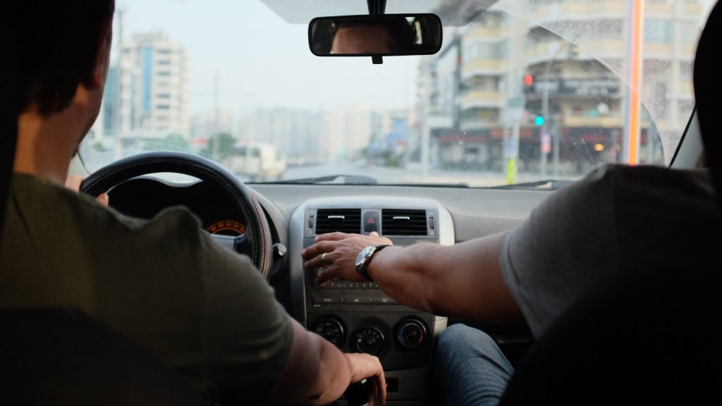 Image of two men in a car, on driving and one adjusting the air conditioning vents.